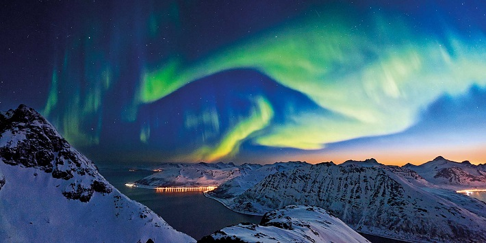 Northern Lights dancing over snow-capped mountains on a fjords cruise
