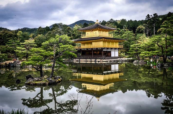 Yellow Japanese temple reflected in water