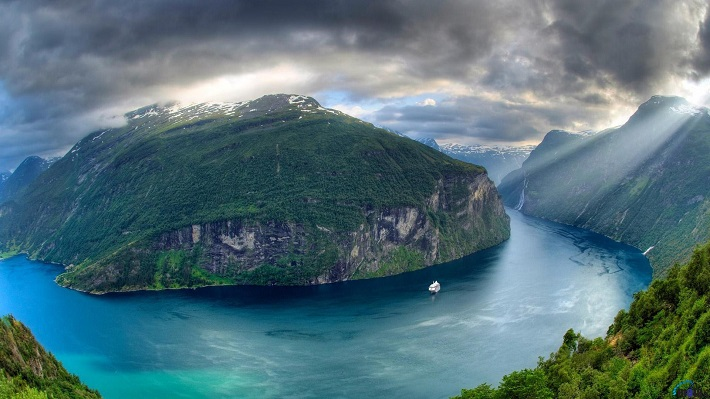 Cruise ship sailings through a Norwegian fjord on a stormy day