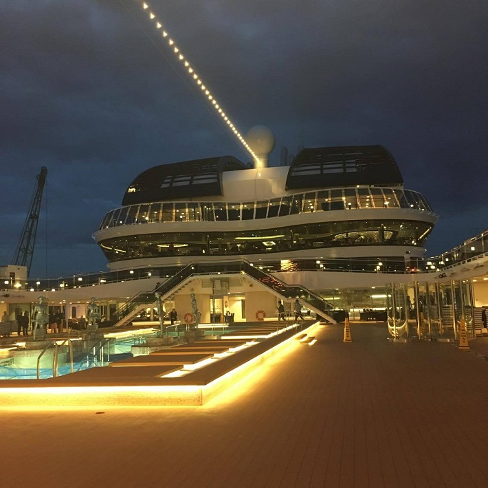 Lights shining out from MSC Meraviglia on the ships pool deck at night