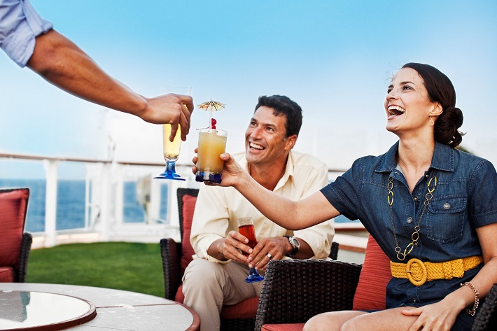 A couple in casual dress enjoying cocktails on a Celebrity Cruises ship