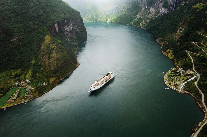Cruise ship sailing through the middle of a Norwegian fjord