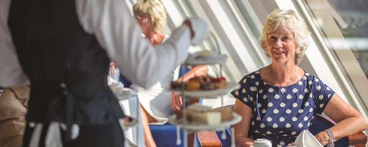 Lady being served afternoon tea on-board Fred. Olsen cruise ship, Balmoral