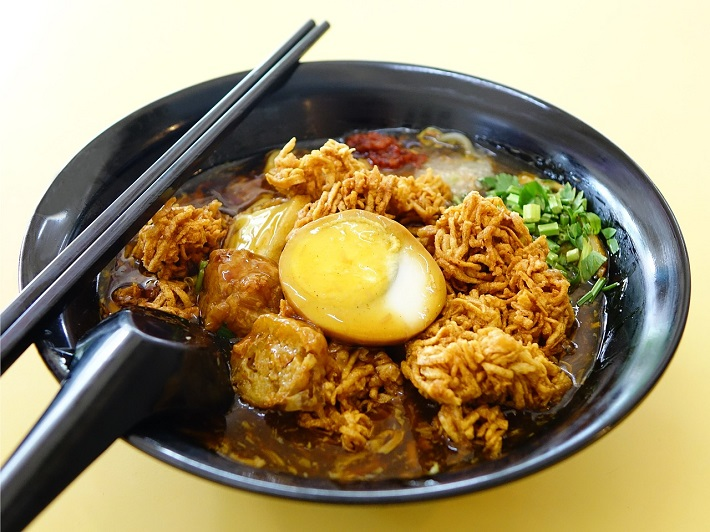 A bowl of lor mee, a common dish in Singapore, with chopsticks balanced on the rim