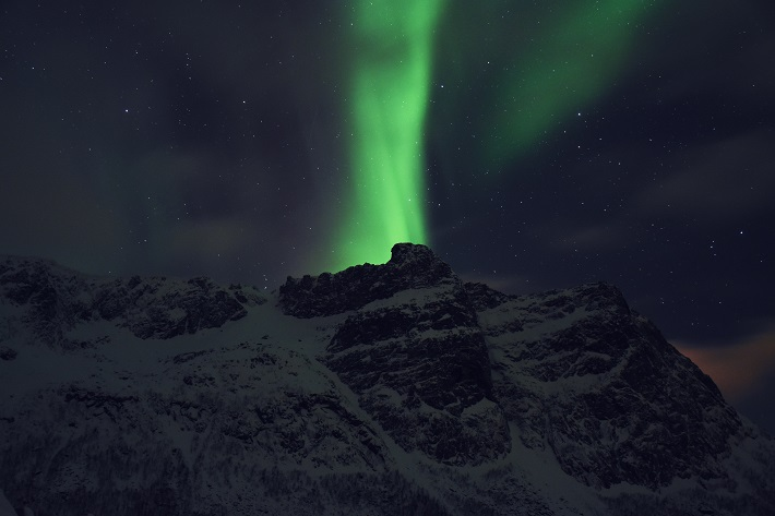 Northern lights shining above a snow-covered mountain in Tromso, Norway
