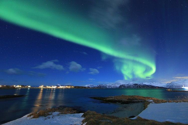 Northern lights shining above mountains and water in Tromso