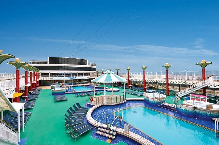 The pool area on-board Norwegian Pearl under a clear blue sky
