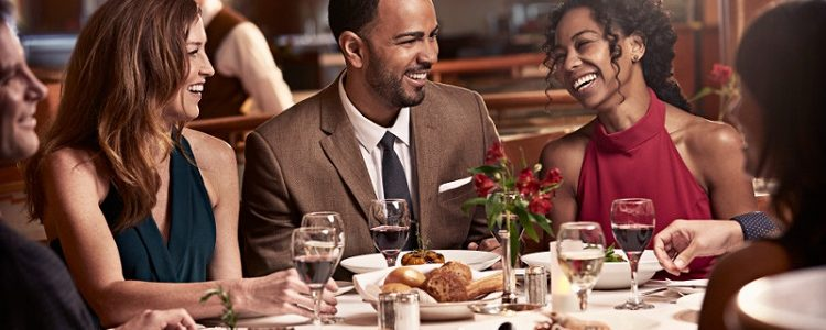 Well-dressed friends enjoying dinner in the main dining on-board Princess Cruises
