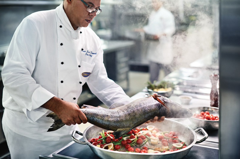 A chef on-board Regal Princess cooking up fresh fish with a pan of vegetables