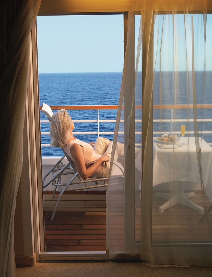 Lady enjoying room service breakfast on her cruise ship balcony