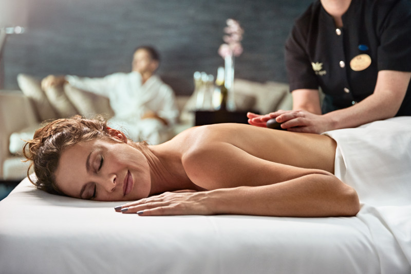 Lady enjoying a hot stone massage in the Lotus Spa on Royal Princess