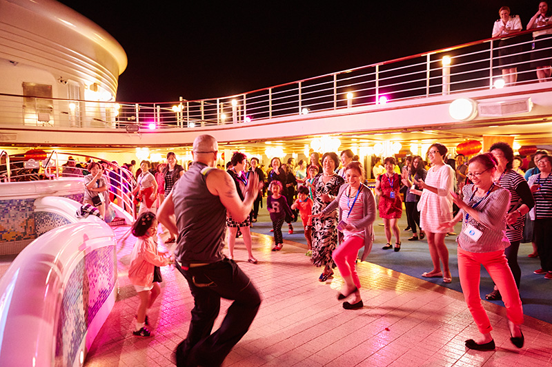 Families dancing on the deck of Sapphire Princess in the evening
