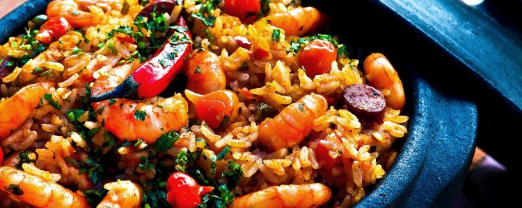 A stone pan of seafood paella with shrimps and peppers