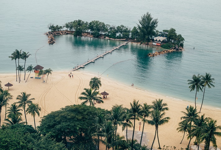 A beach at Sentosa, Singapore, with a walkway leading to a tiny island