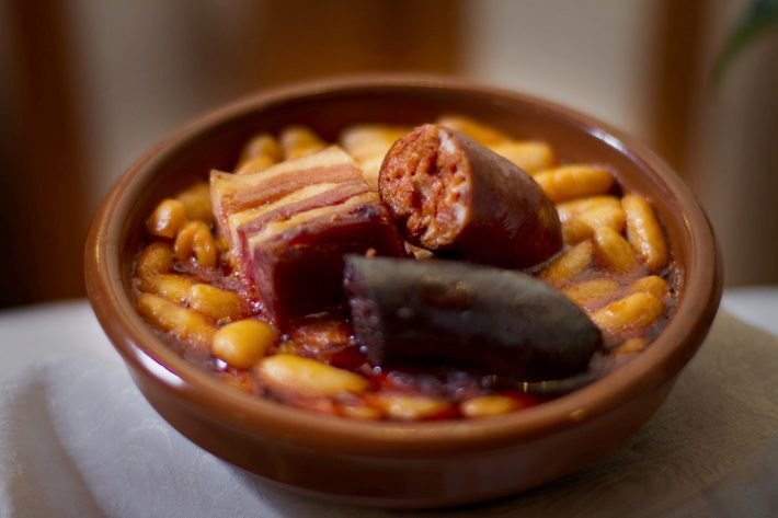 Bowl of Spanish fabada stew complete with black pudding and pork