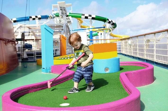 Toddler playing colourful crazy golf on a Carnival Cruise Lines ship