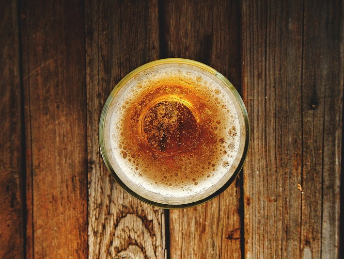 Looking down into a cold glass of craft beer set on top of a wooden table
