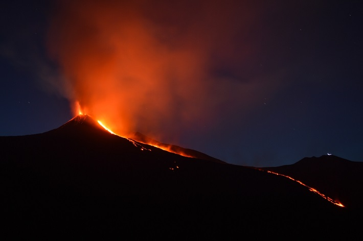 Mount Etna erupting and throwing lava into the black night sky
