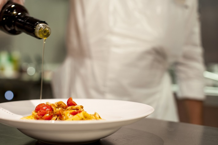 Chef pouring olive oil onto a pasta dish on-board an MSC Cruises ship