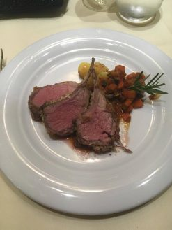 Plate of beef with vegetables and rosemary on-board MSC Meraviglia