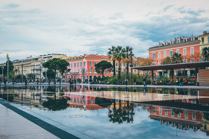 A square in Nice lined with charming buildings and soaked with water from fountains