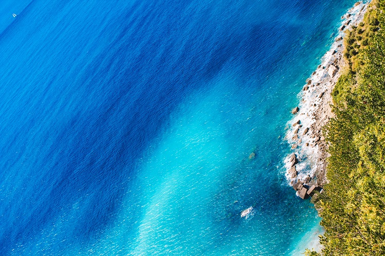 Bright blue sea lapping onto a lush shoreline in the Western Mediterranean