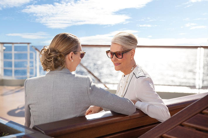 Two elegant female passengers sitting on-deck on a Cunard cruise ship and talking