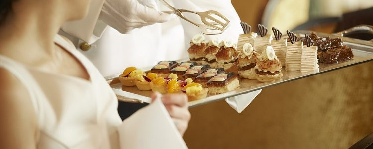 A waiter serving fine afternoon tea to a passenger on-board Cunard's Queen Mary 2 cruise ship