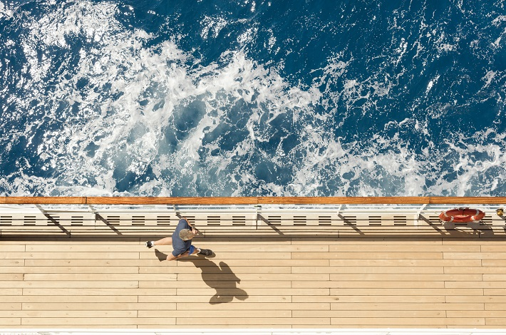 Passenger running on Queen Mary 2's running track as the ship sails through bright blue sea