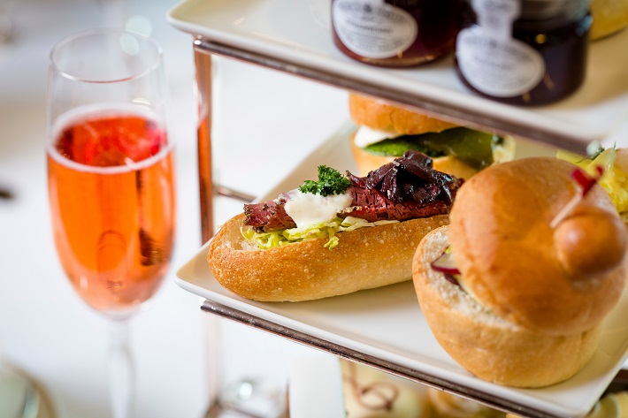 Gourmet sandwiches and a glass of champagne in afternoon tea on-board Cunard Queen Victoria