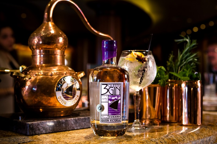 Bottle of Cunard's own brand Three Queen's gin on a bar next to a copper decanter