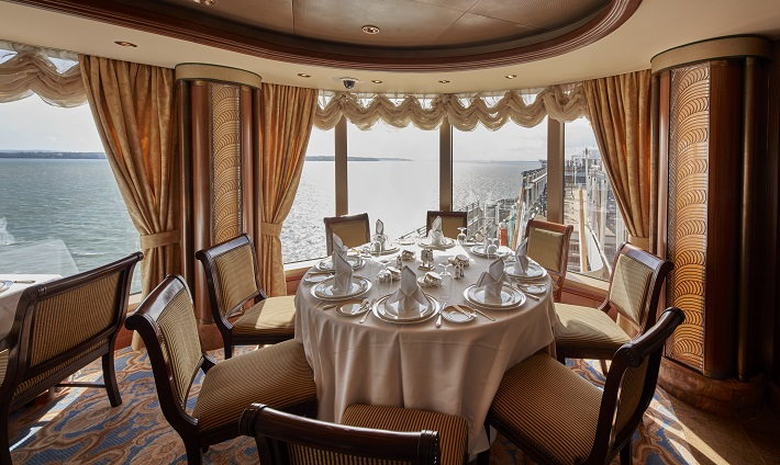 Elegant table next to a picturesque window in the Grills restaurant on-board Queen Victoria