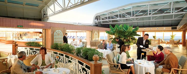 People relaxing in the stunning winter garden area on-board Queen Victoria at sunset