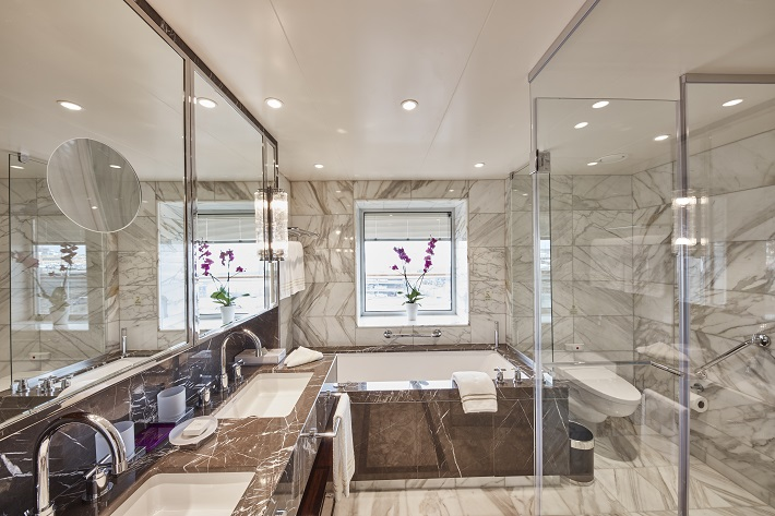 Luxurious marble bathroom with a bath tub and shower on-board Cunard Queen Victoria