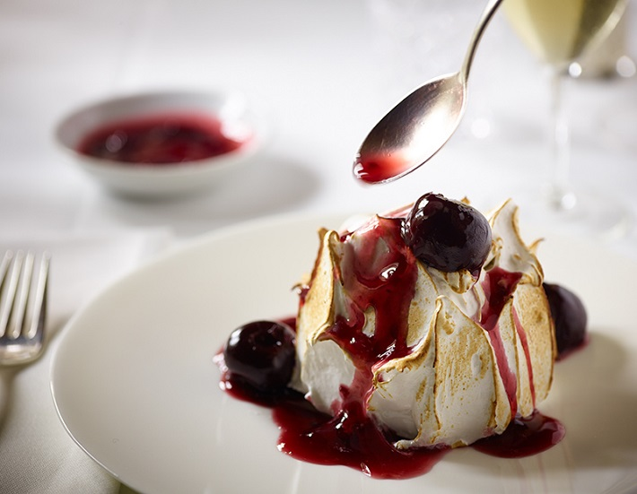 Diner dipping a spoon into a baked Alaska in the Pinnacle dining room on-board Koningsdam
