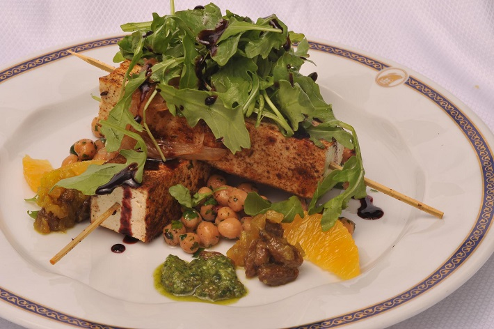 Barbecue tofu skewers on a bed of baked chickpeas and topped with rocket