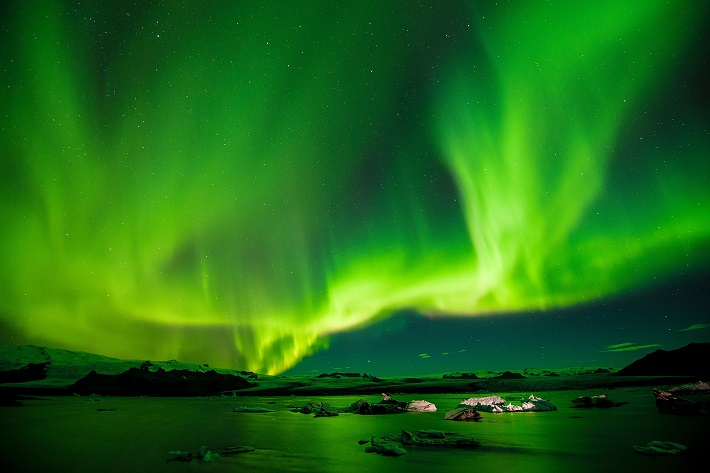 Bright green Northern Lights dancing over water in Iceland