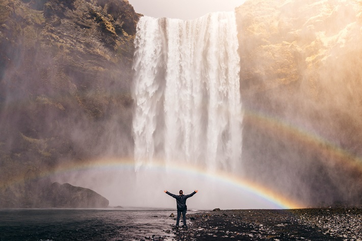 Person standing in front of Skogafoss waterfall in Iceland