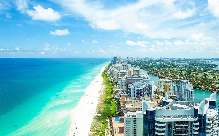 Skyscrapers lining a Miami beach bordered by bright blue sea
