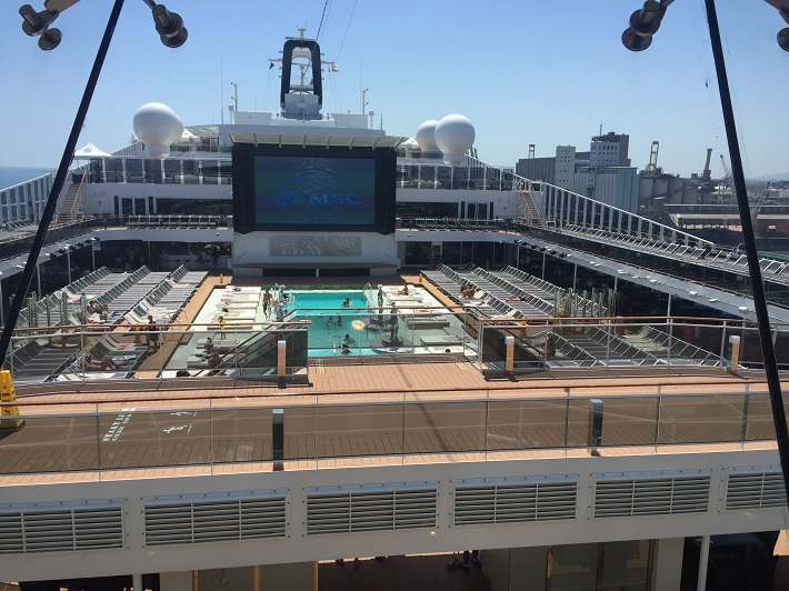 MSC Meraviglia's pool deck, complete with movie screen, bathed in sunshine