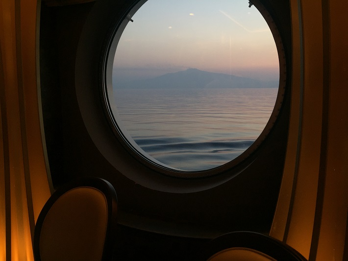 View out of one of MSC Meraviglia's portholes towards Mediterranean mountains as the sun sets
