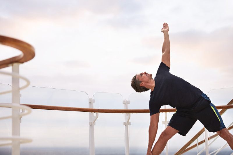 Man stretching during an on-deck yoga class on a Princess Cruises ship