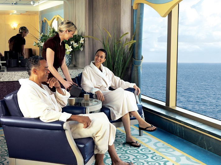 A couple relaxing in plush chairs in front of a sea view in the Queen Victoria spa