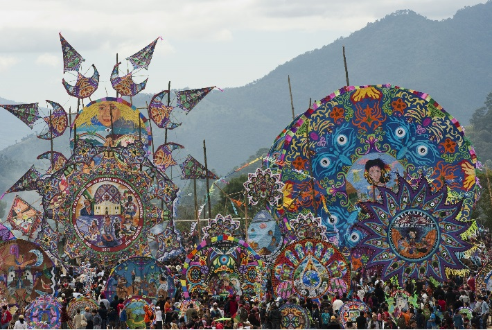 People marching along the road with Barriletes Gigantes kites in Guatemala