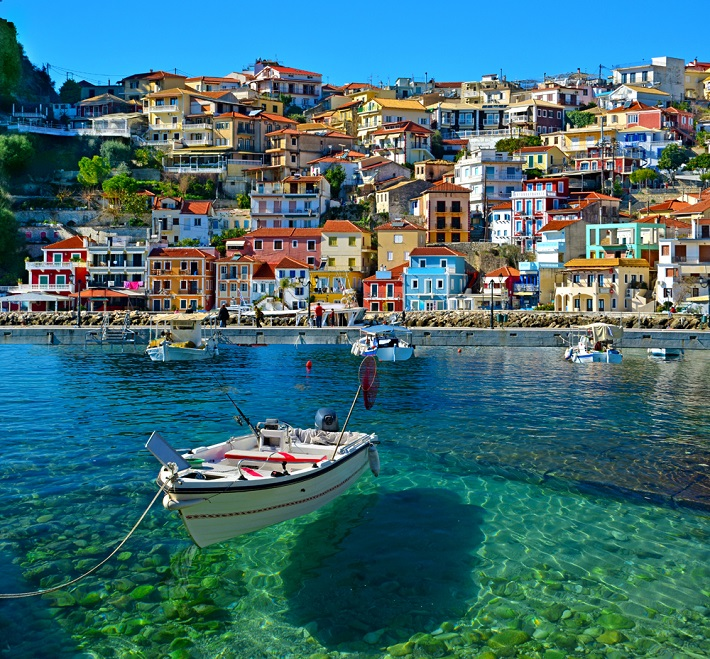 A fishing boat floating on crystal clear water in front of cliffside houses in Corfu