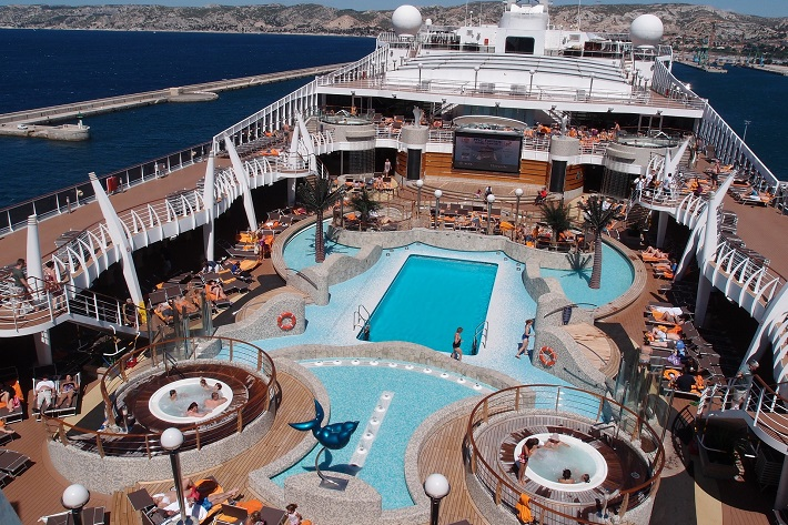 Passengers enjoying the vast pool deck on a cruise ship in the Mediterranean sea