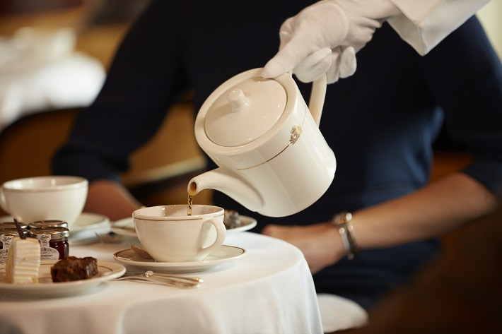 A white-gloved waiter pouring tea for a guest during afternoon tea