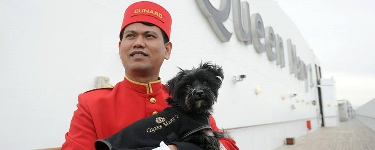 Cunard crew member standing outside the Queen Mary 2 cruise ship and holding a dog