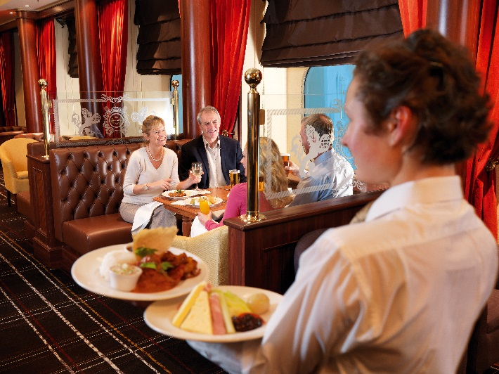 A waiter bringing traditional pub grub to guests in Cunard's Golden Lion pub