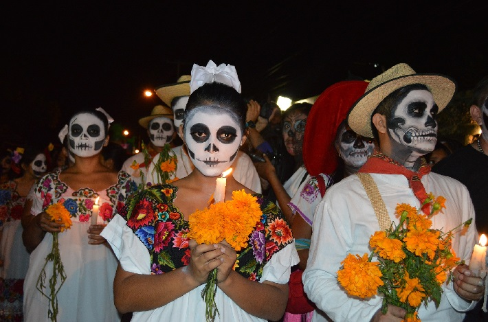 Mexican locals wearing Day of the Dead costumes and carrying yellow marigolds along the street at night